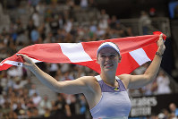 Denmark's Caroline Wozniacki unfurls Denmark's flag after her third-round loss to Tunisia's Ons Jabeur at the Australian Open tennis championship in Melbourne, Australia, on Jan. 24, 2020. (AP Photo/Andy Brownbill)