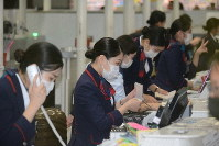 Ground staff at a check-in counter at Narita International Airport in the city of Narita, Chiba Prefecture, are seen using masks. (Mainichi/Tadakazu Nakamura)