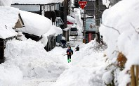 Residents of the Fukui Prefecture city of Katsuyama along the Sea of Japan coast plow snow piled up on a street in their neighborhood in this file photo take in February 2018. (Mainichi/Kentaro Ikushima)
