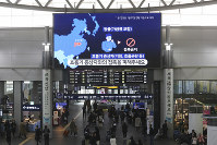 People walk under a screen warning about a new coronavirus at Suseo Station in Seoul, South Korea, on Jan. 24, 2020. (AP Photo/Ahn Young-joon)