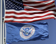 In this July 31, 2014 file photo, the U.S. and U.S. Department of Homeland Security flags fly in Karnes City, Texas. (AP Photo/Eric Gay)