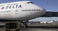 In this Oct. 9, 2012 file photo, Delta Air Lines 747-400 airplane sits parked at Seattle-Tacoma International Airport in Seattle. (AP Photo/Ted S. Warren)