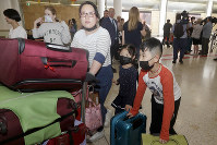 A woman and her children wearing face masks arrive in Sydney on Jan. 23, 2020, from a flight from Wuhan, China. (AP Photo/Rick Rycroft)