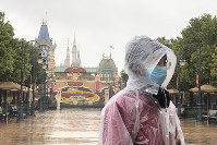 A Disney employee stands in front of the gates of the Shanghai Disney Resort, which announced that it will be closed indefinitely from Saturday, in Shanghai, on Jan. 25, 2020. (AP Photo/Fu Ting)