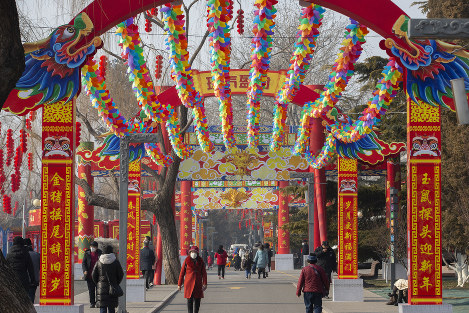 People wearing face masks walk under a canopy decorated with spinning colored fans for a canceled Lunar New Year temple fair at Longtan Park in Beijing, on Jan. 25, 2020. (AP Photo/Mark Schiefelbein)