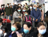 Passengers wearing protective face masks enter the departure hall of a high-speed train station in Hong Kong, on Jan. 24, 2020. (AP Photo/Achmad Ibrahim)