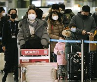Passengers wear masks at Beijing international airport on Jan. 24, 2020, the first day of the Lunar New Year holiday. (Kyodo)