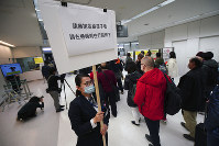 A quarantine officer shows a notice to travelers from China's Wuhan and other cities as they go through body temperature scanners at Narita International Airport in Narita, near Tokyo, on Jan. 23, 2020. (AP Photo/Eugene Hoshiko)