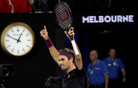 Switzerland's Roger Federer celebrates after defeating Australia's John Millman in their third round match at the Australian Open tennis championship in Melbourne, Australia, on Jan. 25, 2020. (AP Photo/Lee Jin-man)