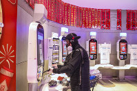A shopper wearing goggles, a face mask and gloves uses a self checkout machine at a supermarket in Wuhan in central China's Hubei province, on Jan. 25, 2020. (Chinatopix via AP)