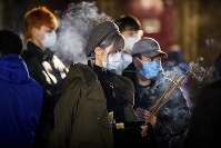 Incense burns as people wear face masks while marking the Lunar New Year at the International Buddhist Temple, in Richmond, B.C., Canada, on Jan. 24, 2020. (Darryl Dyck/The Canadian Press via AP)
