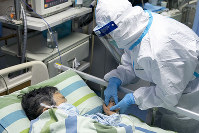 In this Jan. 24, 2020, photo released by China's Xinhua News Agency, a medical worker attends to a patient in the intensive care unit at Zhongnan Hospital of Wuhan University in Wuhan in central China's Hubei Province. (Xiong Qi/Xinhua via AP)