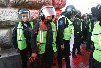 A female police officer covered in red paint stands by during a women's protest against the latest murder of two women, in Mexico City, Saturday, Jan. 25, 2020. (AP Photo/Ginnette Riquelme)