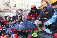 Rescue workers carry a wounded man that was found alive in the rubble of a building destroyed on Friday's earthquake in Elazig, eastern Turkey, Saturday, Jan. 25, 2020. Rescue workers were continuing to search for people buried under the rubble of apartment blocks in Elazig and neighboring Malatya. Mosques, schools, sports halls and student dormitories were opened for hundreds who left their homes after the quake.(Depo Photos via AP)