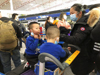 Children adjust their face masks as they wait in line at check-in counters at Beijing Capital International Airport in Beijing, Saturday, Jan. 25, 2020. (AP Photo/Yanan Wang)
