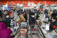 Shoppers wearing face masks pay for their groceries at a supermarket in Wuhan in central China's Hubei province, on Jan. 25, 2020. (Chinatopix via AP)
