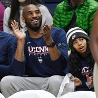 大学バスケットボールのゲームを観戦するコービー・ブライアントさんと娘のジアナさん(右)=2019年3月2日、米コネチカット州で、AP
