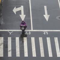 武漢の交差点でスクーターに乗る人=2020年1月25日、AP