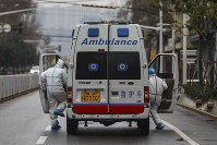 In this Jan. 26, 2020 photo, ambulance crew members in protective gear get into their ambulance in Wuhan in central China's Hubei Province. (Chinatopix via AP)