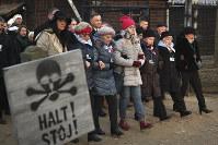 Poland's President Andrzej Duda walks along with survivors through the gates of the Auschwitz Nazi concentration camp in Oswiecim, Poland, on Jan. 27, 2020. (AP Photo/Czarek Sokolowski)