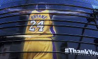 In this April 13, 2016, file photo, a giant banner congratulating Kobe Bryant is draped around Staples Center before his last NBA basketball game in downtown Los Angeles. (AP Photo/Richard Vogel)