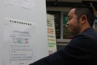 新型コロナウイルス対策で、名古屋城正門前に中国語で書かれた注意喚起のポスターを張る名古屋市の担当者=同市中区で27日、野村阿悠子撮影