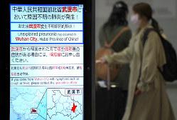 新型コロナウイルスによる肺炎への注意を呼びかける電光掲示板=関西国際空港で24日、久保玲撮影