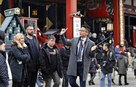 Hato Bus Co. tour guide and interpreter Atsushi Inoue stands in front of a group of foreign tourists in front of Sensoji temple in Tokyo's Taito Ward on Dec. 26, 2019. (Mainichi/Akihiro Ogomori)