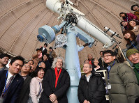 Brian May, center left, is seen after having signed the mount of the telescope at the Kyoto University Kwasan Observatory, during his visit to the facility in Kyoto's Yamashina Ward on Jan. 27, 2020. Professor Kazunari Shibata, center right, the former director of the observatory and who invited May to show his support, is seen standing next to May's signature on the telescope mount. (Mainichi/Ai Kawahira)