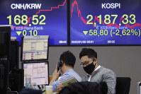 A currency trader wearing a mask watches a calendar at the foreign exchange dealing room of the KEB Hana Bank headquarters in Seoul, South Korea, on Jan. 28, 2020. (AP Photo/Ahn Young-joon)