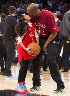 In this Feb. 14, 2016, file photo, Los Angeles Lakers Kobe Bryant kisses his daughter Gianna on the court in warm-ups before first half NBA All-Star Game basketball action in Toronto. (Mark Blinch/The Canadian Press via AP)