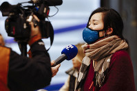A traveler from Beijing speaks to a french TV named BFM TV as she arrives at Charles de Gaulle Airport, north of Paris, early on Jan. 27, 2020. (AP Photo/Kamil Zihnioglu)