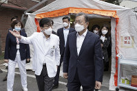 In this photo provided by South Korea Presidential Blue House via Yonhap News Agency, South Korean President Moon Jae-in, right, wearing a mask arrives to inspect the National Medical Center in Seoul, South Korea, on Jan. 28, 2020. (South Korea Presidential Blue House/Yonhap via AP)