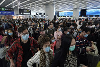 In this Jan. 23, 2020 photo, passengers wear protective face masks at the departure hall of a high-speed train station in Hong Kong. (AP Photo/Kin Cheung)
