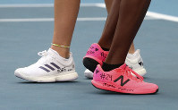 United States' Coco Gauff, right, and compatriot Caty McNally wear a tribute to Kobe Bryant on their shoes during their doubles match against Japan's Shuko Aoyama amd Ena Shibahara at the Australian Open tennis championship in Melbourne, Australia, on Jan. 27, 2020. (AP Photo/Dita Alangkara)