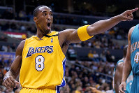 In this Dec. 13, 2002 file photo Los Angeles Lakers' Kobe Bryant points to a teammate during an NBA basketball game in Los Angeles. (AP Photo/Mark J. Terrill)