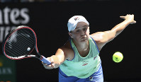 Australia's Ashleigh Barty makes a forehand return to Petra Kvitova of the Czech Republic during their quarterfinal match at the Australian Open tennis championship in Melbourne, Australia, on Jan. 28, 2020. (AP Photo/Dita Alangkara)