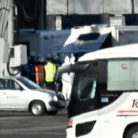中国・武漢から到着したチャーター機から、重症の患者を乗せたと見られる救急車(奥)=羽田空港で2020年1月29日午前10時14分、竹内紀臣撮影