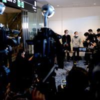 中国・武漢からチャーター機で日本に帰国した人たちを代表して取材に応じる武漢からの帰国者2人(中央奥)=羽田空港で2020年1月29日午前9時51分、宮武祐希撮影