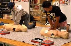 人形を使って、胸骨圧迫による心肺蘇生を練習する人たち。胸の真ん中を強く押す。「ウサギとカメ」の歌や、アニメ「ドラえもん」の主題歌などのリズムに合わせてやるとよいという。