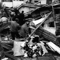 押しつぶされた民家の前で「中に人がいるから早く助けて」と座り込む家人(手前中央)=兵庫県西宮市松生町で1995年1月17日午前7時撮影
