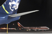 An airplane, background, carrying U.S. citizens being evacuated from Wuhan, China, makes a refueling stop at the north terminal at Ted Stevens Anchorage International Airport in Anchorage, Alaska, Jan. 28, 2020. (Bill Roth/Anchorage Daily News via AP)