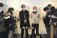 Wearing surgical masks, Takeo Aoyama, center left, an employee at Nippon Steel Corp.'s subsidiary in Wuhan, China, and Takayuki Kato, center right, an employee at an information and communications technology company Intec, speak to journalists after returning home by a Japanese chartered plane at Haneda international airport in Tokyo, on Jan. 29, 2020. (AP Photo/Haruka Nuga)