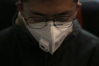 A man wears a mask as he travels on a train, on Jan. 29, 2020, in the Odaiba district of Tokyo. (AP Photo/Jae C. Hong)