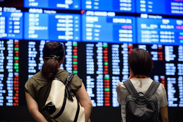 東証の株価ボードを見る個人投資家(Bloomberg)