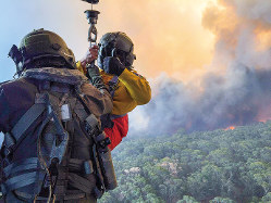 軍のヘリから降下する消防隊員(豪国防軍提供)