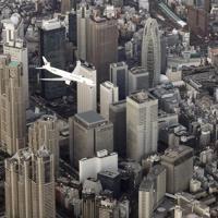 羽田空港の新飛行ルートの実機飛行確認が始まり、都心上空を飛行する航空機=東京都渋谷区で2020年2月2日午後4時49分、本社ヘリから