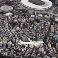 羽田空港の新飛行ルートの実機飛行確認が始まり、都心上空を飛行する航空機。上は国立競技場=東京都渋谷区で2020年2月2日午後4時49分、本社ヘリから