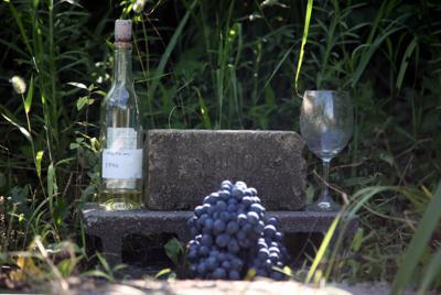 ワインボトルやワイングラス、そしてコンクリートブロックが置かれた故仲村光夫さんが眠る場所=2019年8月、大阪府羽曳野市小ケ谷地区で