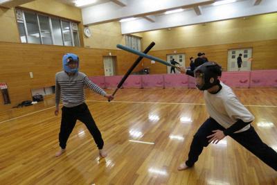 世界2位の川瀬春人さんとスポーツチャンバラで対戦する記者(左)=岐阜県垂井町の県立不破高で